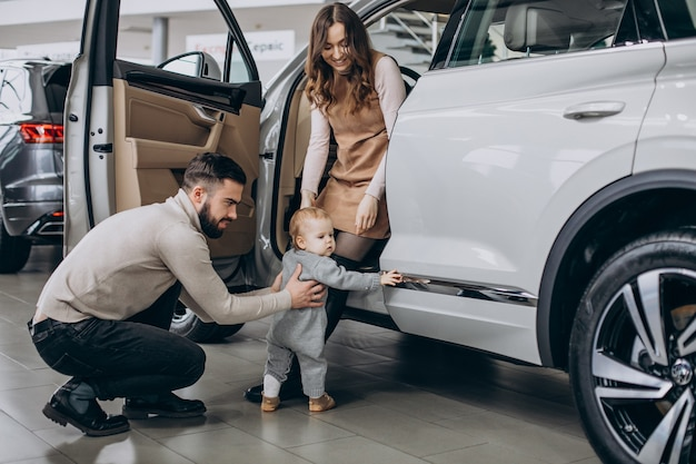 Familie met schattige dochter die een auto kiest in een autoshowroom
