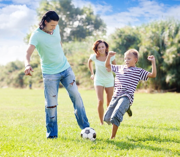 Familie met tiener kind spelen met voetbal