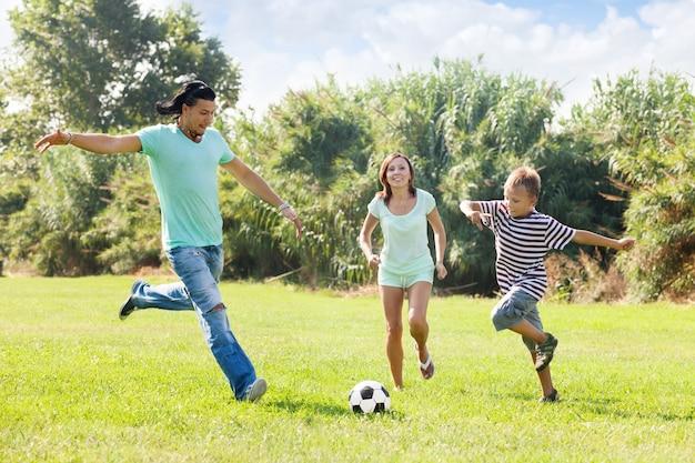 Familie met tiener spelen in voetbal