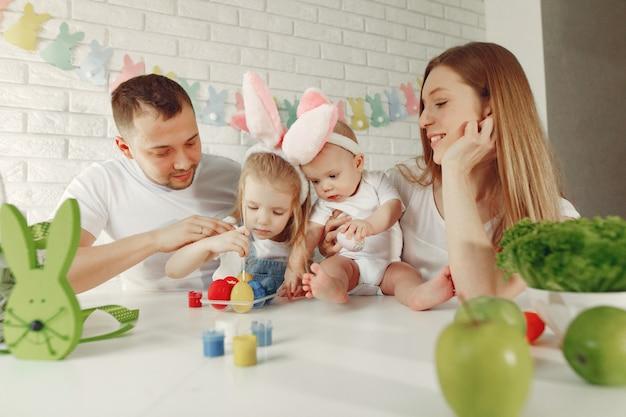 Familie met twee jonge geitjes in een keuken die aan pasen voorbereidingen treft