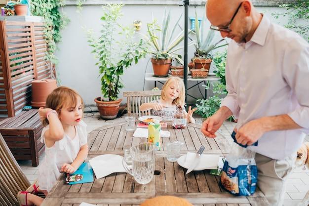Familie met vrouwelijke lijst van de kinderen de openluchtzitting die ontbijt heeft