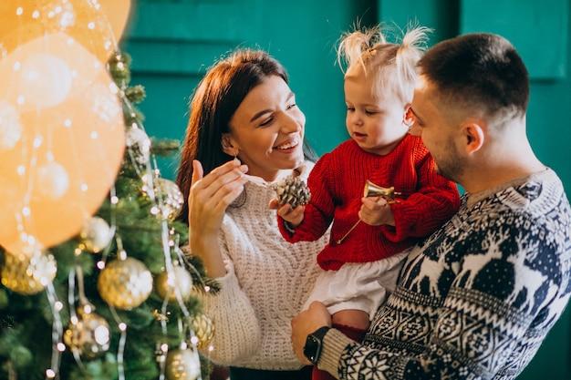 Familie met weinig dochter hangend speelgoed op kerstboom