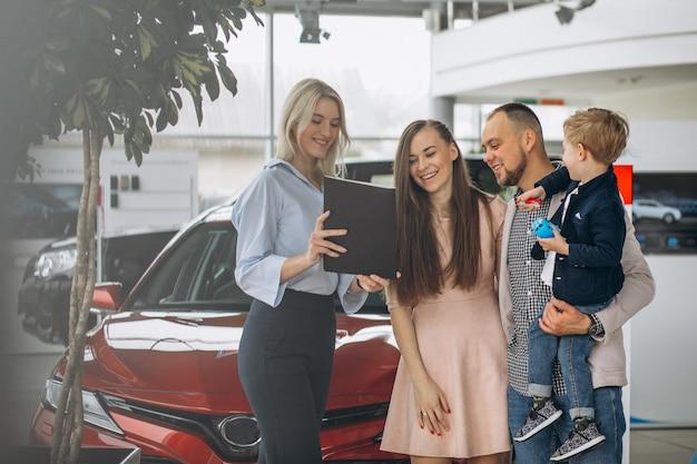 Familie met zoon die een auto in een autotoonzaal kiest