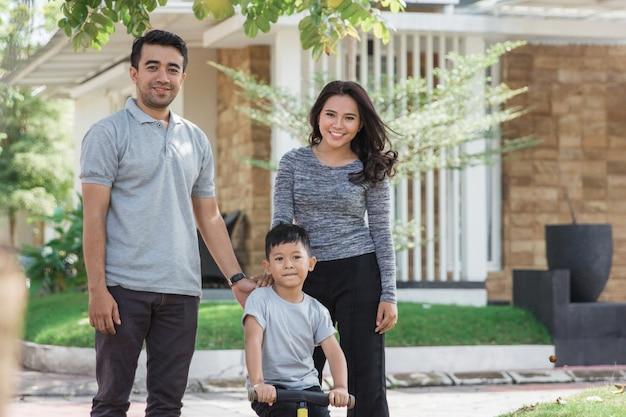 Familie met zoon die een fiets berijdt