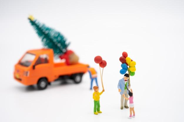 Familie miniatuurmensen die zich op kerstboom bevinden vier kerstmis