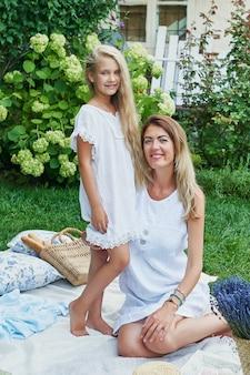 Familie moeder en dochter in de tuin in de zomer op een picknickrust