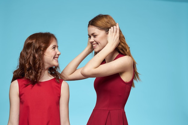 Familie moeder en dochter knuffel rode jurken communicatie emoties blauw