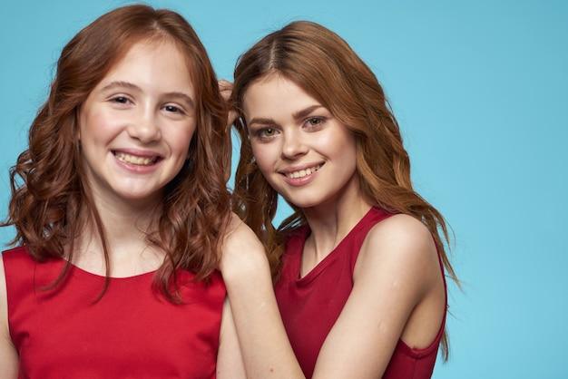 Familie moeder en dochter knuffel rode jurken communicatie emoties blauwe achtergrond