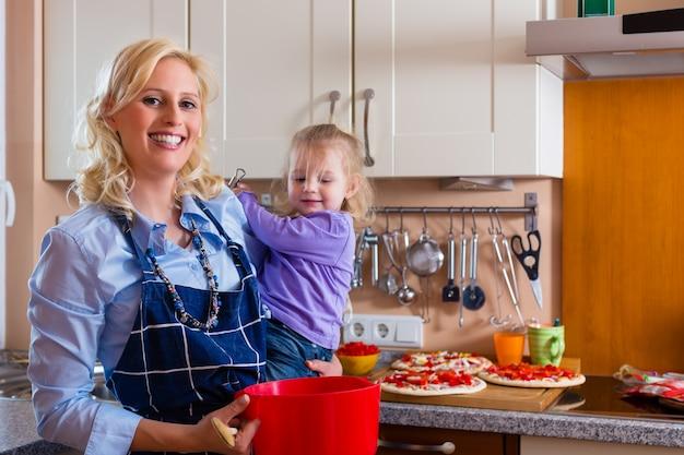 Familie - moeder en kind pizza bakken