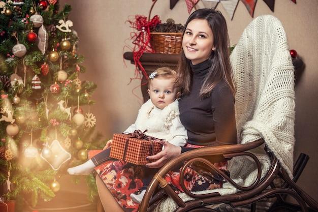 Familie moeder en kinderen met cadeautjes in mooie dozen in het kerstinterieur