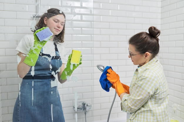 Familie moeder en tienerdochter die samen thuis in de badkamer schoonmaken. kind helpt ouder, huishouden, levensstijl, huishoudelijk werk