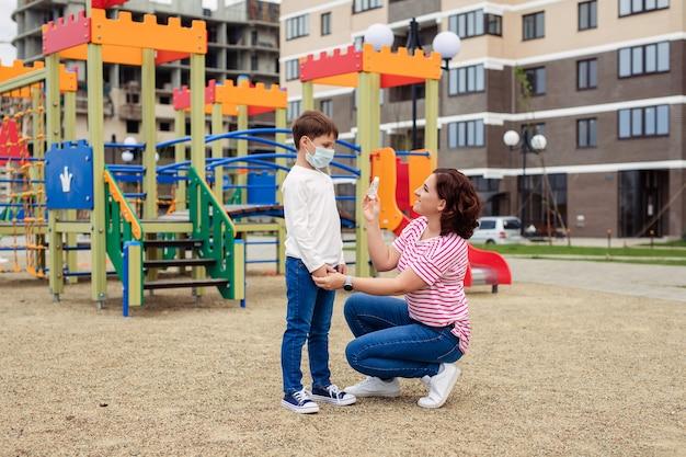 Familie moeder en zoon op de speelplaats. het kind draagt een beschermend medisch masker tijdens een epidemisch coronair virus of griep. persoonlijke beschermingsmiddelen. moeder geeft hand antisepticum aan haar baby