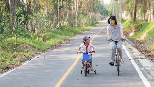 Familie. moeder en zoon rijden in het park