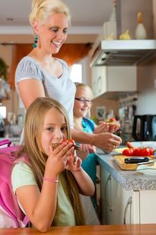 Familie, moeder maakt ontbijt voor school