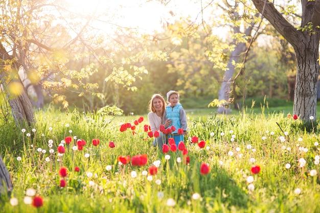 Familie moeder met dochter vrouw met kind in de lente staan en knuffelen op een open plek met groen gras en tulpen bij zonsondergang