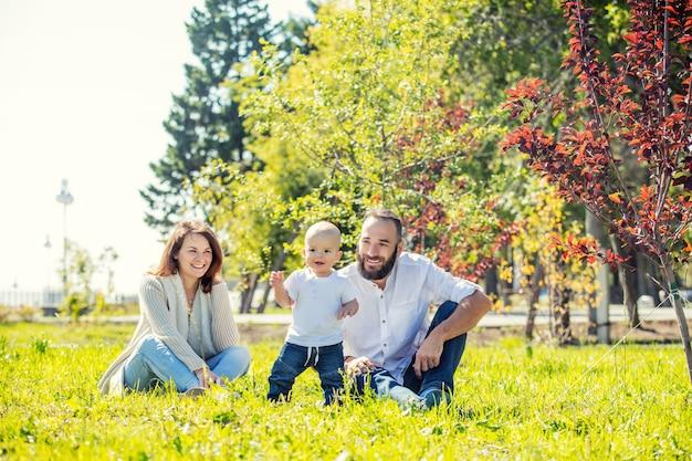 Familie moeder vader en baby blij met een glimlach samen buiten in het park zomer portret