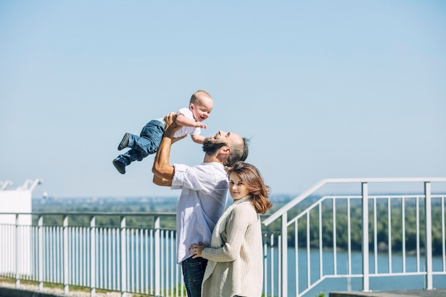 Familie moeder vader en baby blij met een glimlach samen in het park wandelen langs de promenade in zomer portret