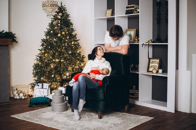 Familie, moeder, vader en baby thuis in de buurt van een kerstboom