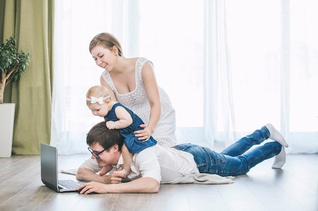 Familie moeder, vader en dochter met een laptop samen thuis gelukkig en mooi