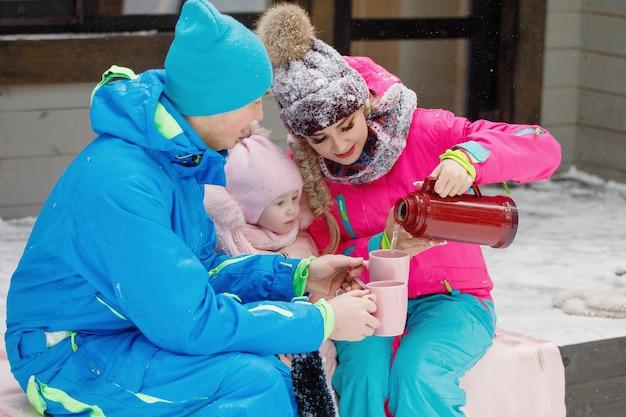 Familie - moeder, vader en dochter schenken in de winter bij het huis hete thee uit een thermoskan in een kopje buiten.