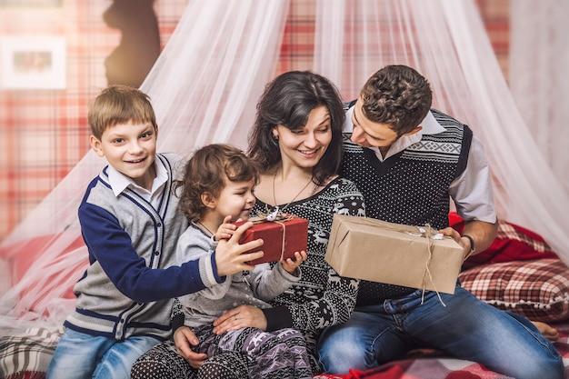 Familie moeder vader en kinderen geven elkaar cadeaus in je huis winter decor