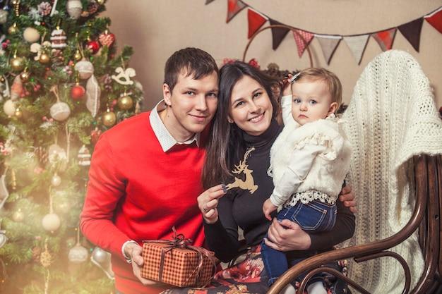 Familie moeder vader en kinderen met cadeautjes in mooie dozen in het kerstinterieur