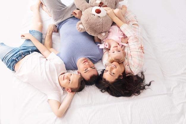 Familie moeder vader zoon en dochtertje thuis samen gelukkig liggend op het bed bovenaanzicht