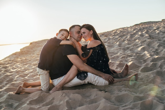 Familie moeder vader zoon in een omhelzing op het strand in de zomer bij zonsondergang