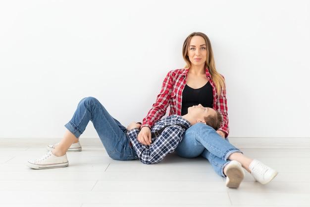 Familie, moeders dag en tiener concept - portret van moeder en zoon zittend op de vloer