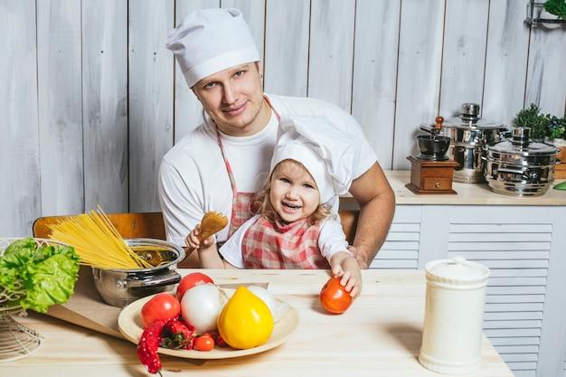 Familie, mooie dochter vader thuis de keuken lachen en samen eten bereiden