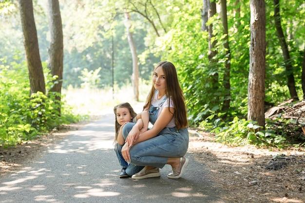 Familie, natuur en mensen concept - moeder en dochtertje brengen samen tijd door tijdens een wandeling in het bos
