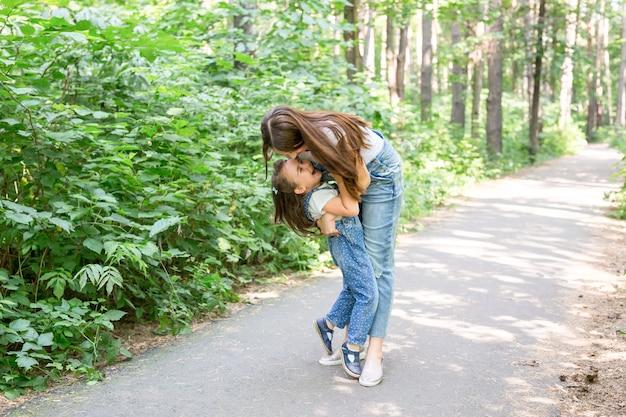 Familie, natuur, mensen concept - moeder en dochter knuffelen in het park