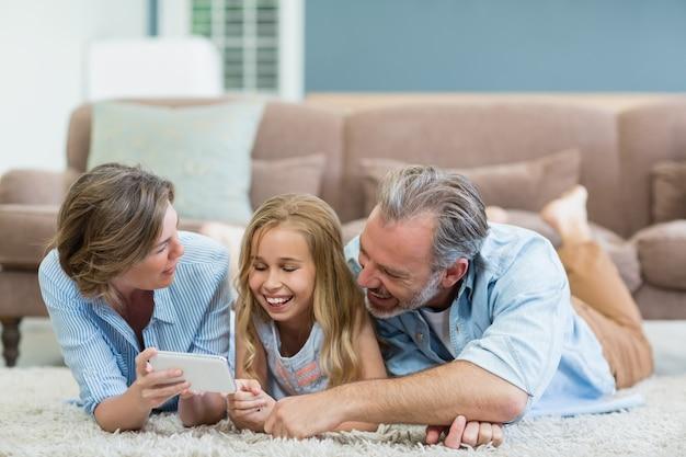 Familie nemen selfie vanaf mobiele telefoon terwijl ze samen op tapijt in de woonkamer liggen
