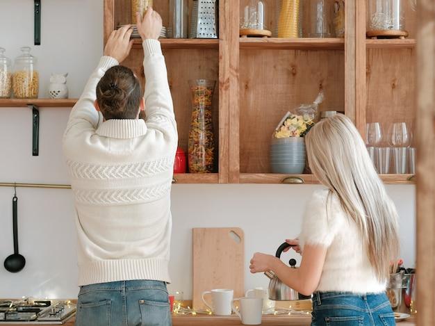 Familie ochtend. paar samen koken in moderne keuken met houten meubilair.