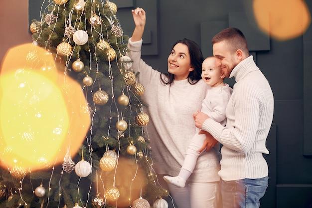Familie om thuis te zitten in de buurt van de kerstboom