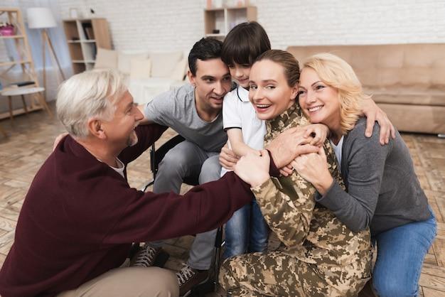 Familie omhelst een meisje dat terugkeerde uit het leger.