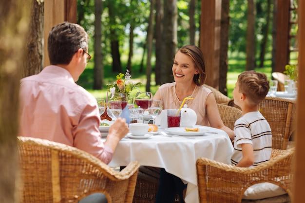 Familie ontbijt. breed glimlachende moeder voelt zich zeer gedenkwaardig tijdens het familieontbijt buiten het huis