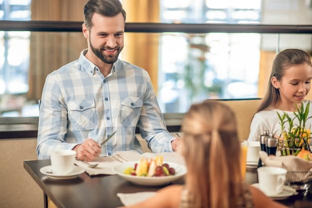 Familie ontbijt. kinderen en hun vader zitten aan de tafel in het restaurant