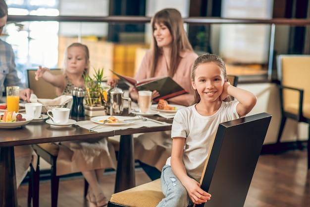 Familie ontbijt. lief meisje, zittend aan de tafel in het restaurant met familie