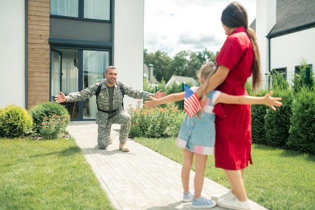 Familie ontmoeten. militaire man die op zijn knie staat terwijl hij vrouw en dochter ziet na een half jaar dienst