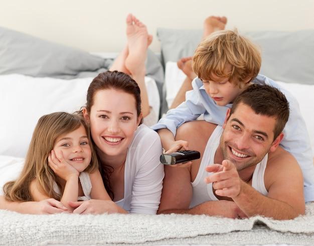 Familie ontspannen in bed en met behulp van een afstandsbediening