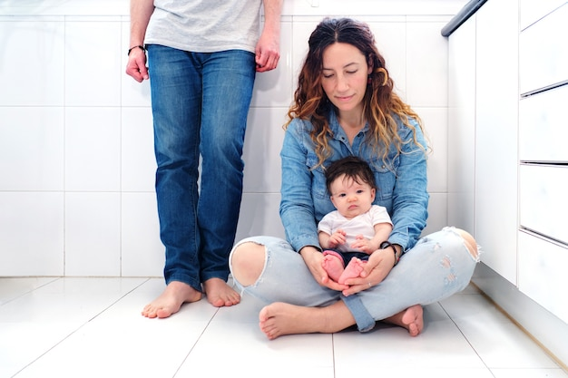 Familie ontspannen in de keuken van het appartement met babymeisje op haar moeder