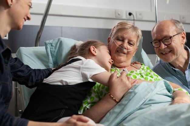 Familie op bezoek bij zieke gepensioneerde senior vrouw in ziekenhuisafdeling