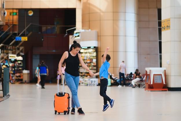 Familie op de luchthaven voor de vlucht. moeder en zoon wachten om aan boord te gaan bij de vertrekpoort van de moderne internationale terminal. reizen en vliegen met kinderen. moeder met kind aan boord van vliegtuig. gele familie