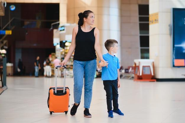 Familie op de luchthaven voor de vlucht. moeder en zoon wachten om aan boord te gaan bij de vertrekpoort van de moderne internationale terminal. reizen en vliegen met kinderen. moeder met kind aan boord van vliegtuig. gele familie Premium Foto