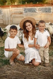 Familie op een boerderij. mensen spelen met geiten. moeder met zoon.