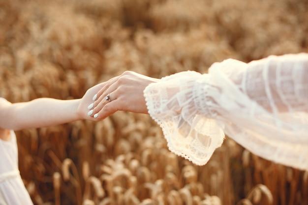 Familie op een zomergebied. sensuele foto. schattig klein meisje. vrouw in een witte jurk.