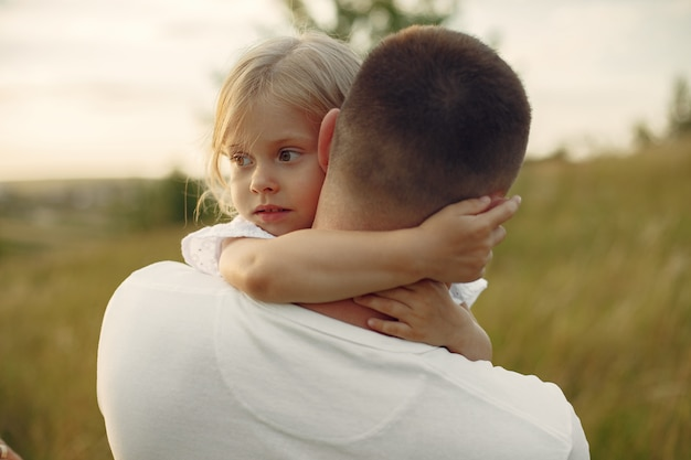 Familie op een zomergebied. vader in een wit overhemd. leuke dochter.