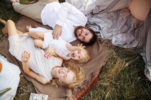 Familie op een zomerpicknick. liggen in het veld, bovenaanzicht