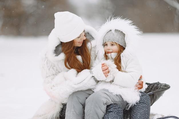 Familie op familie kerstvakantie. vrouw en meisje in een park. mensen met slee.